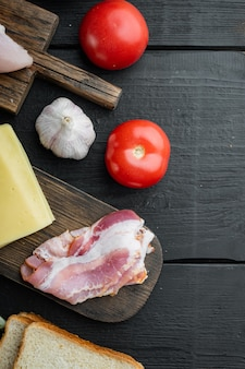 Ingredientes frescos para un sabroso sándwich, sobre fondo de madera negra, vista superior con espacio para copiar texto