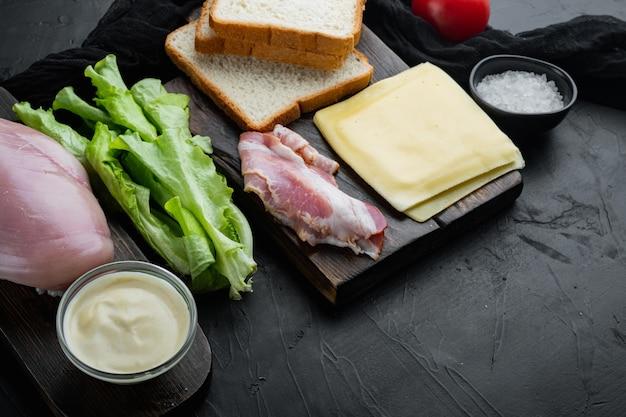 Ingredientes frescos para un sabroso sándwich, sobre fondo negro con espacio para copiar texto