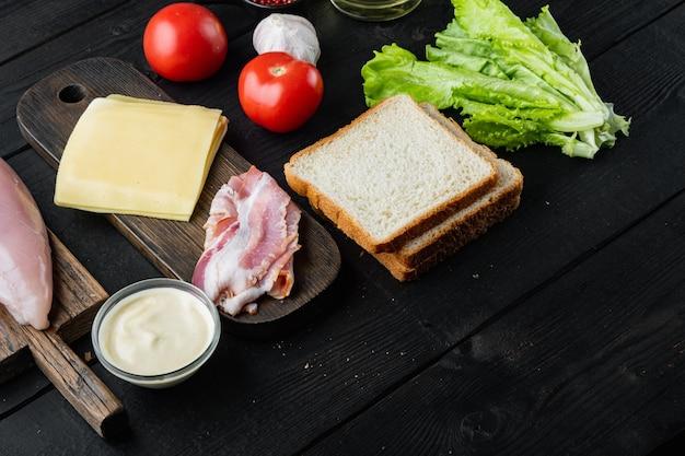 Ingredientes frescos para sabroso sándwich, sobre mesa de madera negra