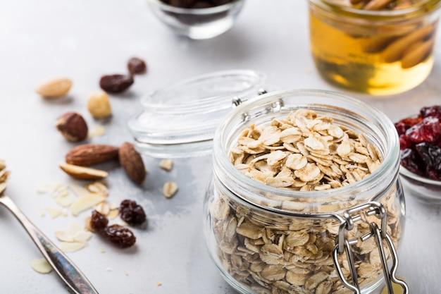 Ingredientes para granola casera de avena en frasco de vidrio.