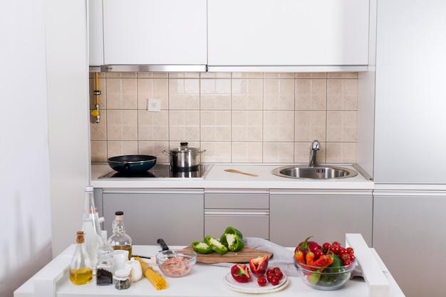 Ingredientes para hacer los espaguetis en mesa blanca en la cocina