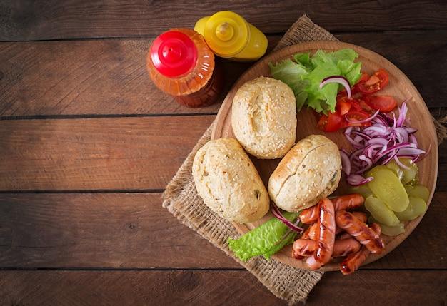 Ingredientes para hacer hot dog - sandwich con pepinillos, cebolla roja y lechuga sobre fondo de madera. vista superior