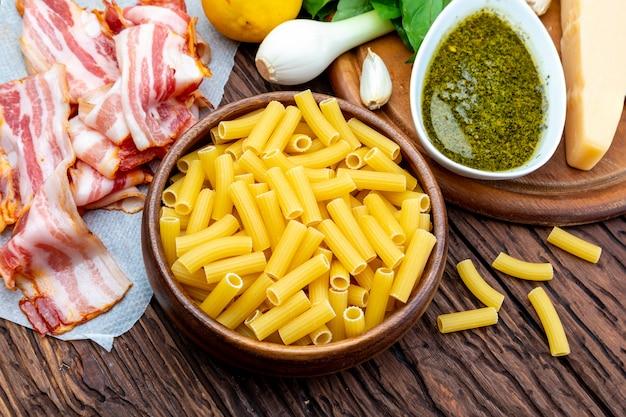 Ingredientes para hacer macarrones con pesto casero. con cebolla y tocino, queso, albahaca, piñones, ajo.