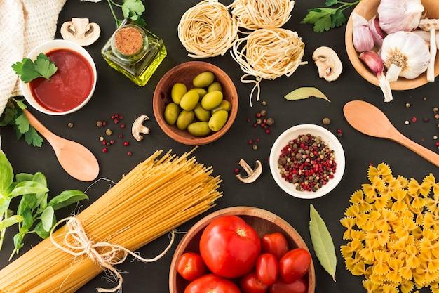 Ingredientes para hacer pasta tagliatelle y espagueti sobre fondo negro