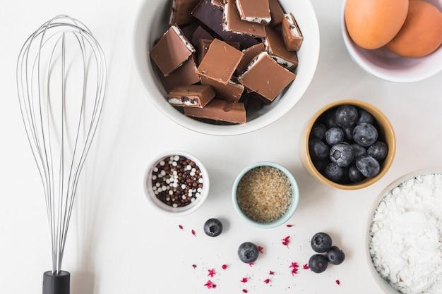 Ingredientes para hacer pastel con batidor sobre fondo blanco