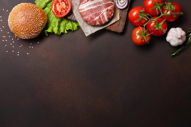 Ingredientes de hamburguesa chuleta cruda, tomates, lechuga, pan, queso, pepinos y cebolla