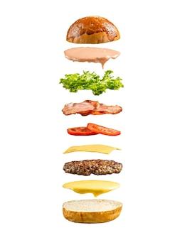 Ingredientes de hamburguesa flotante aislado en el blanco