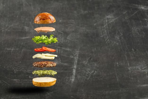 Ingredientes de hamburguesa flotante sobre el fondo gris
