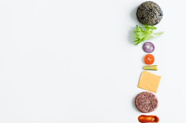 Ingredientes para la hamburguesa negra sobre fondo blanco.
