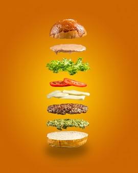 Ingredientes de hamburguesa pesto flotante en la pared amarilla