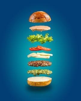 Ingredientes de hamburguesa pesto flotante en la pared azul