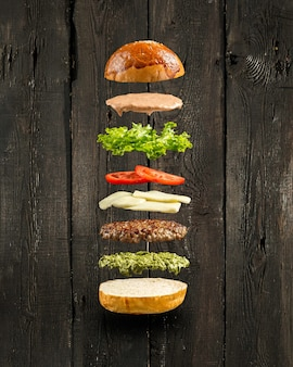 Ingredientes de hamburguesa pesto flotante en la pared de madera