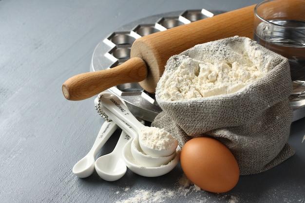 Ingredientes y herramientas para hacer pelmeni ruso sobre fondo gris