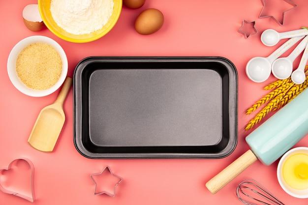 Ingredientes para hornear y bandeja de horno vacía en la mesa rosa