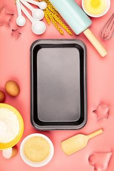 Ingredientes para hornear y bandeja de horno vacía sobre fondo rosa, plano