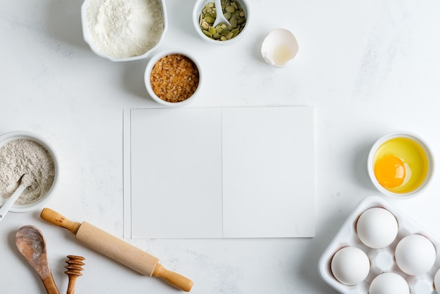 Ingredientes para hornear para cocinar pan tradicional casero con papel para receta en una mesa de mármol gris claro.