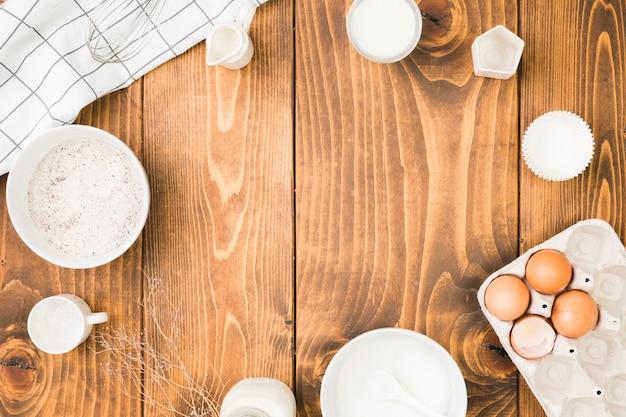 Ingredientes para hornear frescos organizan en marco circular sobre mesa de madera