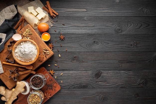 Ingredientes para hornear galletas de jengibre en una pared de madera rústica, vista desde arriba
