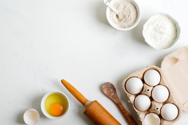 Ingredientes para hornear para hacer pan o pasteles caseros tradicionales en una mesa de mármol gris claro.