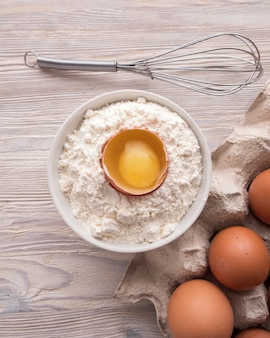 Ingredientes para hornear: harina, huevos y yema en una mesa.