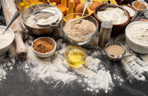 Ingredientes para hornear masa sobre fondo negro, harina, huevos, mantequilla, azúcar y utensilios de cocina para repostería casera. banner de concepto de cocina con espacio de copia de texto