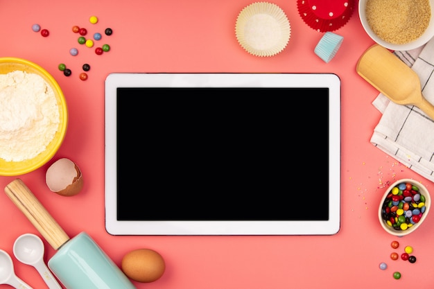Ingredientes para hornear con tableta vacía sobre fondo rosa, endecha plana