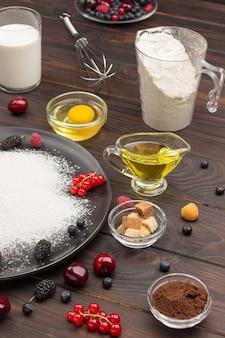 Ingredientes para hornear tarta de frutos rojos. harina en plato negro, cacao en polvo. taza de medir con harina, vaso de leche, huevo roto y sal, batidor de metal sobre la mesa. superficie de madera oscura. vista superior