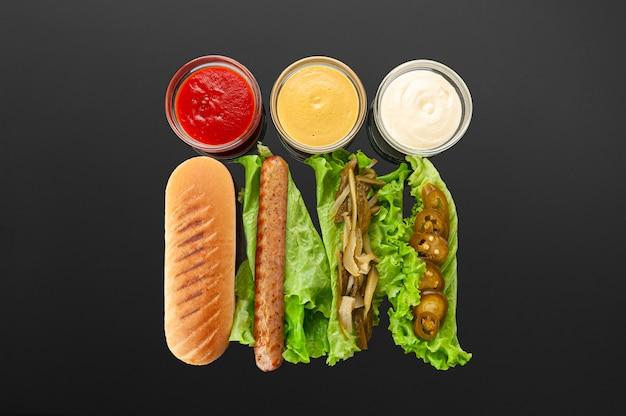 Ingredientes de hot dog en mesa oscura