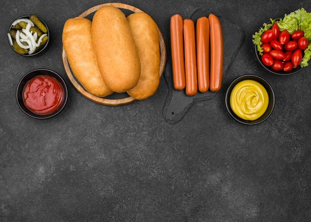 Ingredientes de hot dog sobre fondo de estuco
