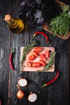 Ingredientes para lecho, tomate en rodajas, chiles picantes, albahaca y aceite vegetal