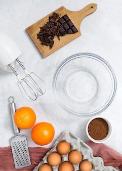 Ingredientes; mezclador eléctrico; rallador de mano y tazón vacío para preparar la torta de chocolate en superficie blanca