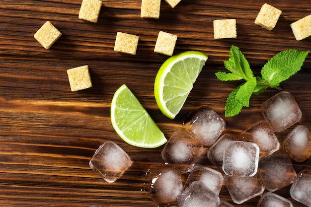 Ingredientes para mojito en una mesa de madera marrón. cubitos de hielo, menta, lima y caña de azúcar.