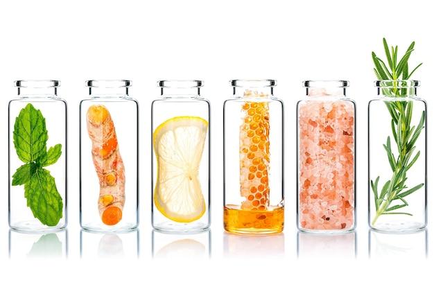 Ingredientes naturales alternativos para el cuidado de la piel en botellas de vidrio aíslan sobre fondo blanco.