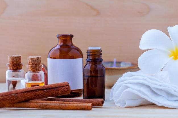 Ingredientes naturales del balneario y botella de aceite esencial en fondo de madera.