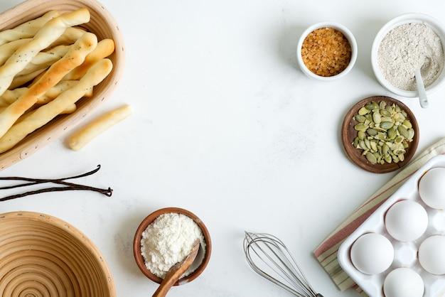 Ingredientes orgánicos naturales para hornear pan o pasteles caseros tradicionales en una mesa de mármol gris claro.