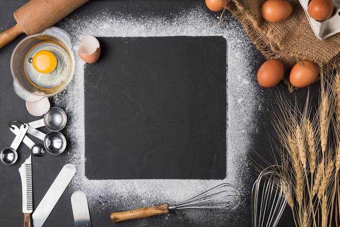 Ingredientes para hornear: huevo y harina en el tablero negro.