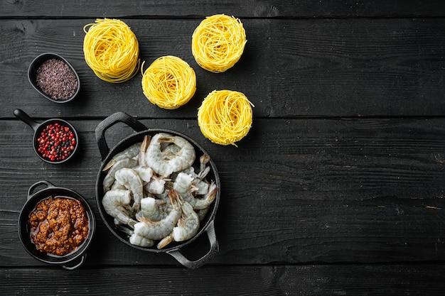 Ingredientes de pasta de langostinos al pesto, sobre mesa de madera negra, vista superior plana, con espacio de copia