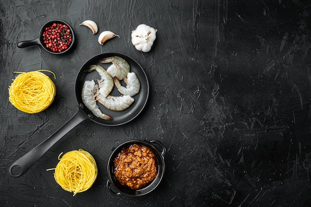 Ingredientes de pasta de langostinos al pesto, sobre una mesa de piedra negra, vista superior plana, con espacio de copia