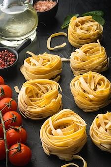 Ingredientes de la pasta tagliatelle con ingredientes de comida italiana, sobre mesa de piedra negra