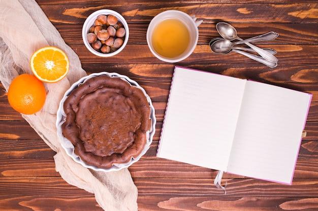 Ingredientes para pastel de chocolate con cucharas y diario blanco sobre el escritorio de madera