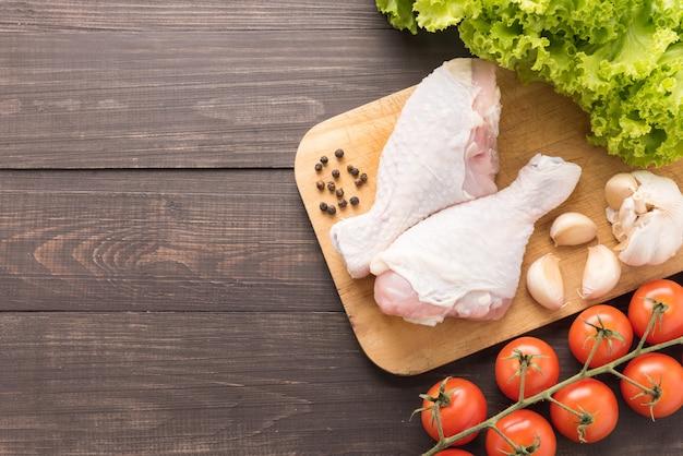 Ingredientes y pierna de pollo crudo en tabla de cortar en mesa de madera