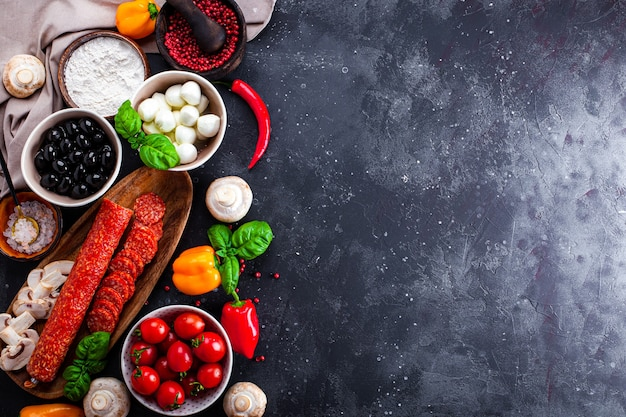 Ingredientes de la pizza en el fondo gris oscuro. la salchicha de pepperoni, el queso mozzarella, los tomates, las aceitunas, los champiñones y la harina son productos diferentes para hacer pizza y pasta.