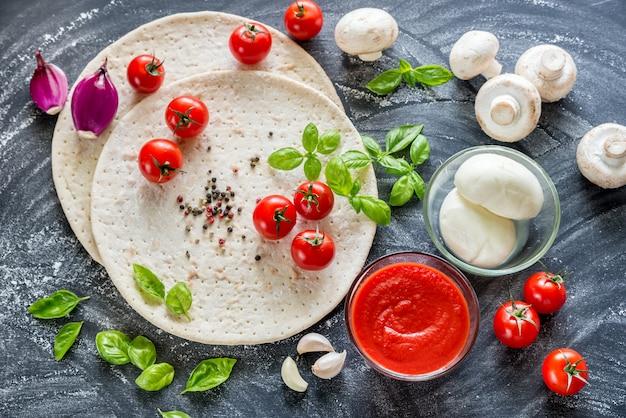 Ingredientes de pizza en la mesa de madera oscura