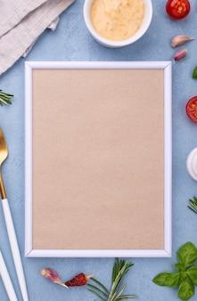 Ingredientes planos y marco en la mesa