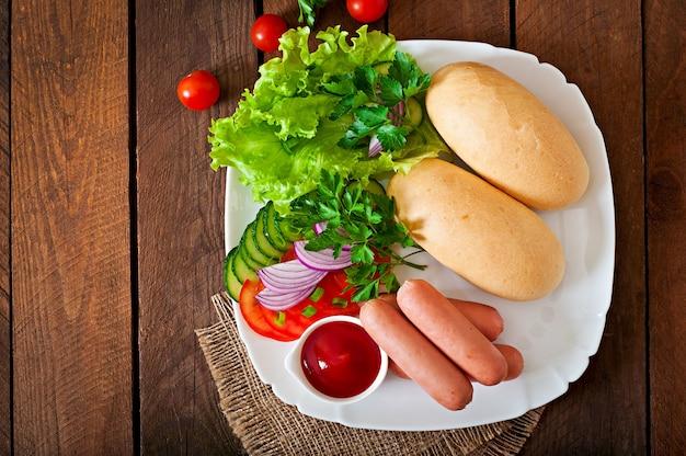 Ingredientes para la preparación de hot dogs en un plato blanco.