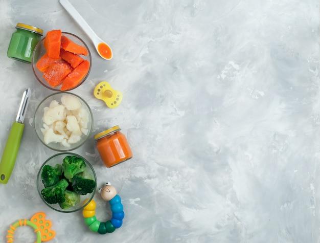 Ingredientes para puré de verduras sobre fondo gris.