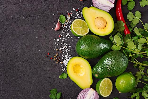 Ingredientes de la salsa de guacamole: aguacate, cebolla, pimiento, ajo, cilantro, lima sobre fondo negro. vista superior