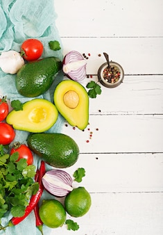 Ingredientes de la salsa de guacamole: aguacate, tomate, cebolla, pimiento, ajo, cilantro, lima sobre fondo blanco. vista superior