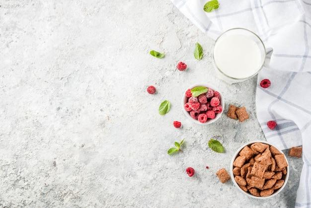 Ingredientes saludables para el desayuno. cereal de desayuno, vaso de leche o yogurt, frambuesas