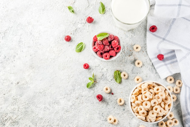 Ingredientes saludables para el desayuno. cereales para el desayuno anillos de maíz leche o yogur frambuesas de vidrio y menta sobre fondo de piedra gris